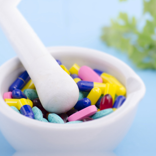 Assorted tablets, pills and capsules inside a white mortar and pestle