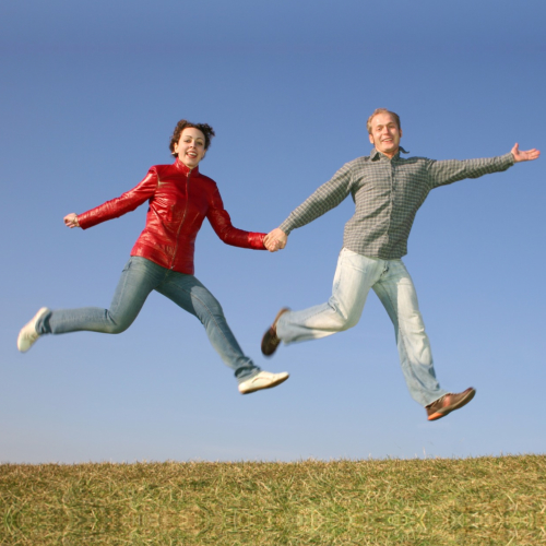 couple holding hands jumping